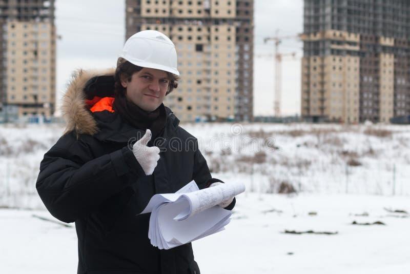 Μηχανικός που στέκεται στο υπόβαθρο μιας νέας πολυκατοικίας χτισμένο σπίτι Μηχανικός σε ένα κράνος με τα έγγραφα μέσα στοκ εικόνες με δικαίωμα ελεύθερης χρήσης