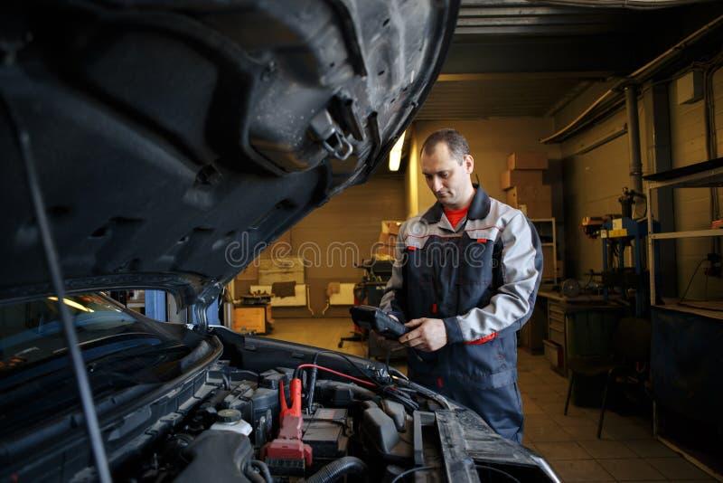 Μηχανικός που χρησιμοποιεί τα συμπληρωματικά καλώδια στο ξεκίνημα μια μηχανή αυτοκινήτων στοκ εικόνα