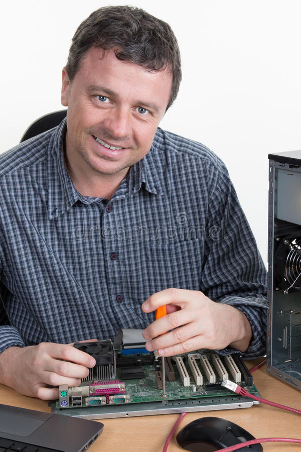 Μηχανικός υπολογιστών που επισκευάζει το υλικό στο φωτεινό γραφείο στοκ εικόνα