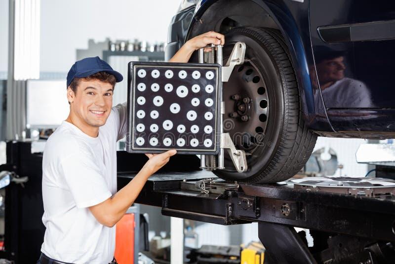 Μηχανικός χρησιμοποιώντας ευθυγραμμιστής ροδών στο αυτοκίνητο στοκ εικόνα με δικαίωμα ελεύθερης χρήσης