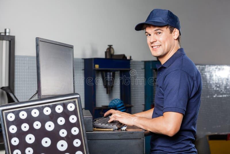 Μηχανικός χρησιμοποιώντας υπολογιστής στο αυτόματο κατάστημα επισκευής στοκ φωτογραφίες με δικαίωμα ελεύθερης χρήσης