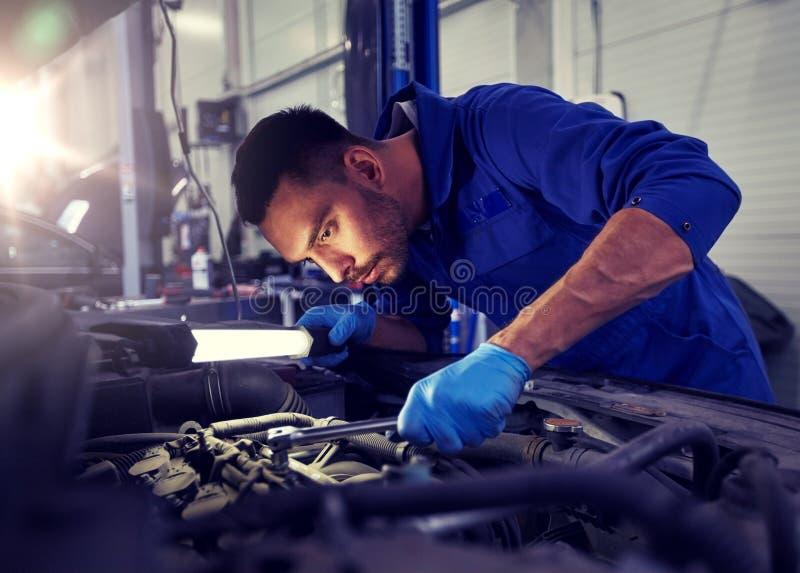 Μηχανικό άτομο με το λαμπτήρα που επισκευάζει το αυτοκίνητο στο εργαστήριο στοκ φωτογραφίες