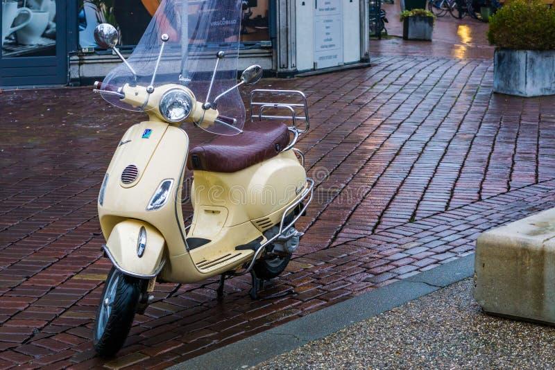 Μηχανικό δίκυκλο Vespa που σταθμεύουν στις οδούς πόλεων, δημοφιλής αστική μεταφορά, καλά - γνωστό εμπορικό σήμα από την Ιταλία, κ στοκ φωτογραφίες