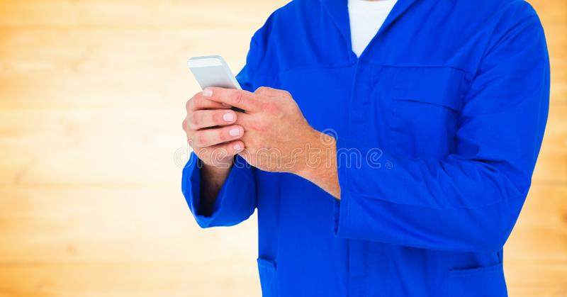 Μηχανικό να κρατήσει ψηλά τηλέφωνο ενάντια στη μουτζουρωμένη κίτρινη ξύλινη επιτροπή στοκ φωτογραφία