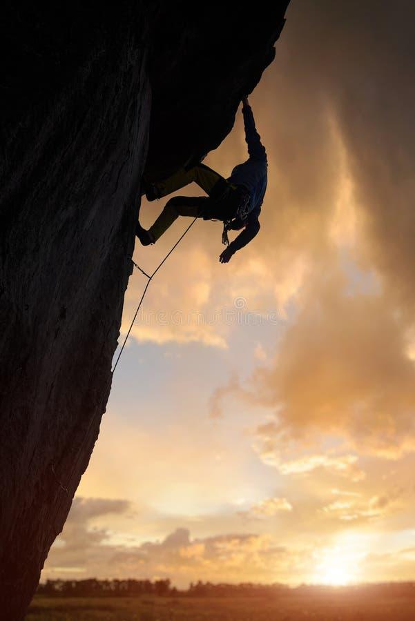 Μη αναγνωρίσιμος αναρριχητής βράχων που προσκολλάται στο βράχο με το ένα χέρι, κοιτάζοντας κάτω Ηλιοβασίλεμα στον θολό ουρανό Χαμ στοκ φωτογραφία με δικαίωμα ελεύθερης χρήσης