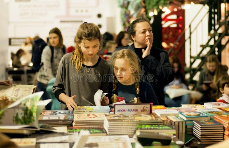 Μη αναγνωρισμένα κορίτσια που διαβάζουν τα βιβλία στο θάλαμο παιδιών του 6ου διεθνούς ΟΠΛΟΣΤΑΣΙΟΥ ΒΙΒΛΙΩΝ φεστιβάλ στοκ φωτογραφία