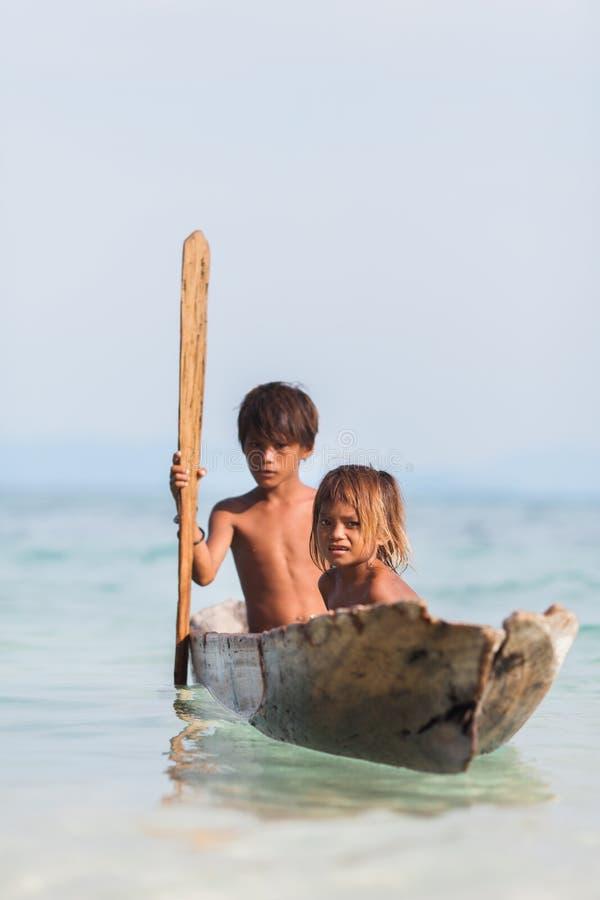 Μη αναγνωρισμένα παιδιά στα κανό στο νησί Mabul στοκ φωτογραφία