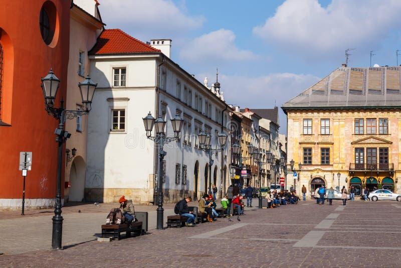 Μη αναγνωρισμένοι τουρίστες που επισκέπτονται το μικρό τετράγωνο αγοράς στην Κρακοβία, Πολωνία στοκ φωτογραφία