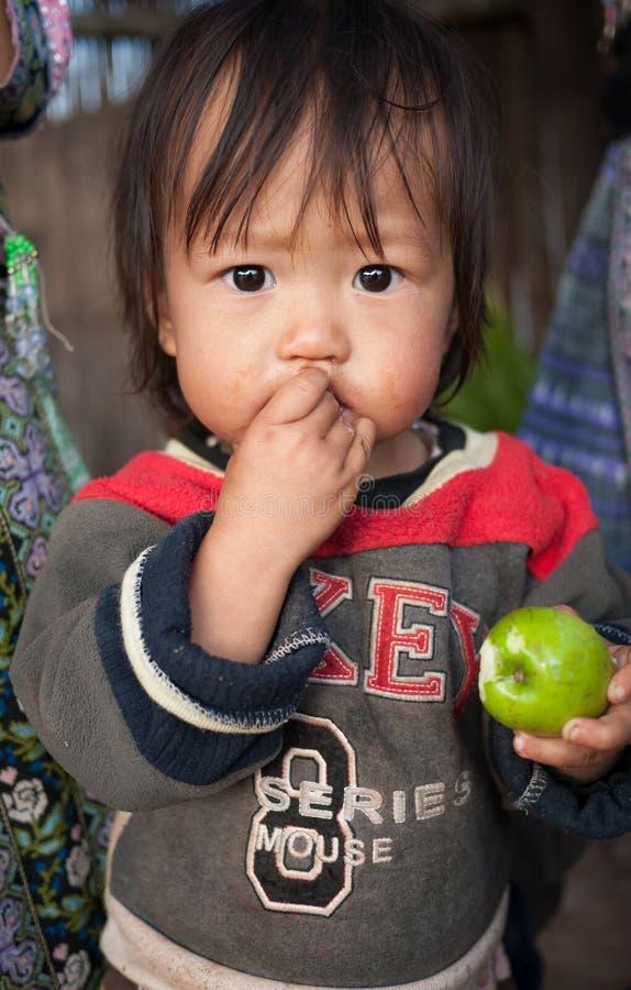 Μη αναγνωρισμένο μικρό αγόρι της Karen που τρώει το μήλο πιθήκων στοκ εικόνες