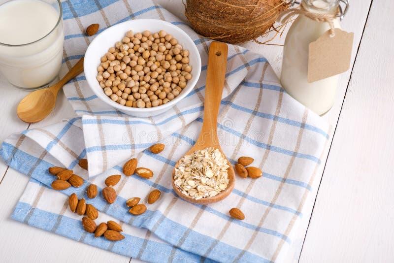 Μη γαλακτοκομικό γάλα Vegan στα συστατικά εναλλακτικών λύσεων γυαλιού και γάλακτος όπως ένα καρύδι, αμύγδαλο, σόγια, βρώμη στον ά στοκ εικόνα με δικαίωμα ελεύθερης χρήσης