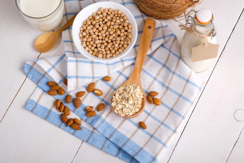 Μη γαλακτοκομικό γάλα Vegan στα συστατικά εναλλακτικών λύσεων γυαλιού και γάλακτος όπως ένα καρύδι, αμύγδαλο, σόγια, βρώμη στον ά στοκ φωτογραφίες