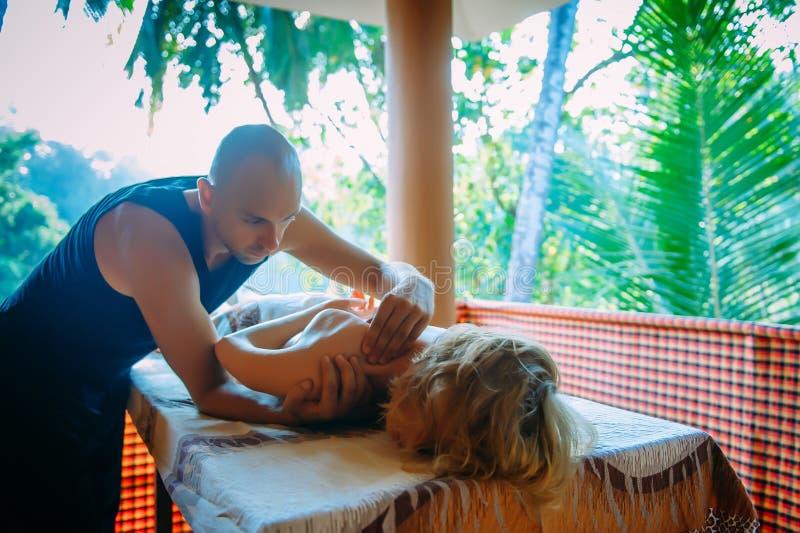 Μη παραδοσιακό μασάζ ευεξίας σε εξωτερικό χώρο Ο νεαρός λεπτός μασέρ κάνει μασάζ στον ώμο, στο χέρι και στον ώμο μιας γυναίκας στοκ φωτογραφία