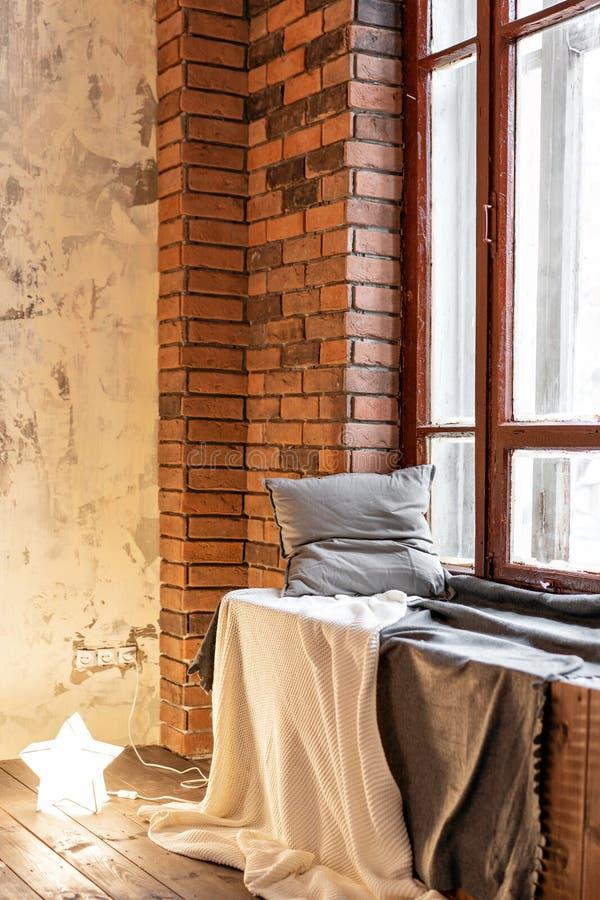 Μια άνετη θέση στο windowsill, με τα μαξιλάρια και ένα πλεκτό κάλυμμα Διαμερίσματα σοφιτών, τουβλότοιχος με τα κεριά και στοκ φωτογραφία