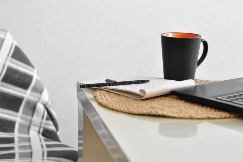 Μια άνετη καρέκλα με ένα κάλυμμα και ένα lap-top, φλιτζάνι του καφέ, σημείωση, μάνδρα σε έναν άσπρο πίνακα κουζινών On-line ψωνίζ στοκ φωτογραφία