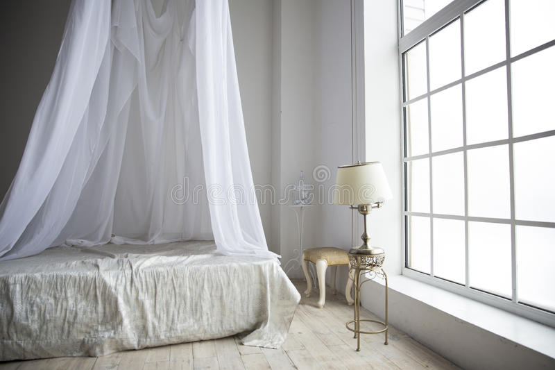 Μια άνετη κρεβατοκάμαρα στα χρώματα κρητιδογραφιών με ένα μεγάλο κρεβάτι, ένας επιτραπέζιος λαμπτήρας ο στοκ εικόνες με δικαίωμα ελεύθερης χρήσης