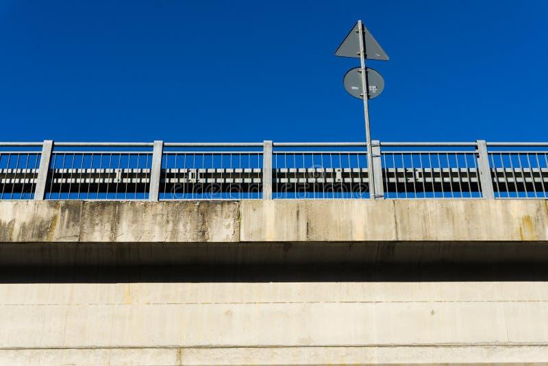 Μια άποψη ενός κιγκλιδώματος συγκεκριμένων δρόμων με το οδικό σημάδι στοκ φωτογραφία