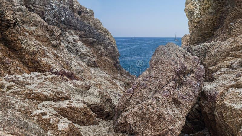 Μια άποψη της μπλε θάλασσας με ένα ενιαίο γιοτ στην απόσταση από τους βράχους στην ακτή η Καταλωνία de lloret χαλά την Ισπ&alpha στοκ εικόνες