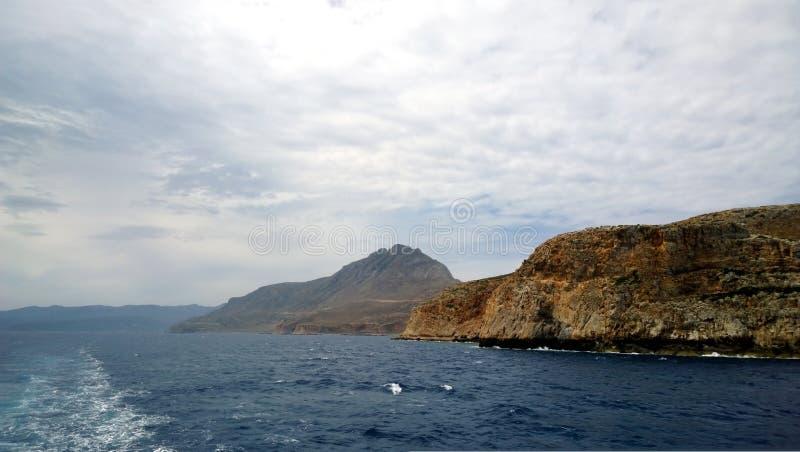 Μια άποψη της δύσκολης ακτής με τη διάβαση του σκάφους Νερό, κύματα, ένα ίχνος του σκάφους, βουνά στην υδρονέφωση στοκ εικόνες με δικαίωμα ελεύθερης χρήσης