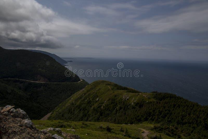 Μια άποψη του Ατλαντικού Ωκεανού που κοιτάζει μετά από μερικούς πράσινους καλυμμένους λόφους στοκ φωτογραφία με δικαίωμα ελεύθερης χρήσης