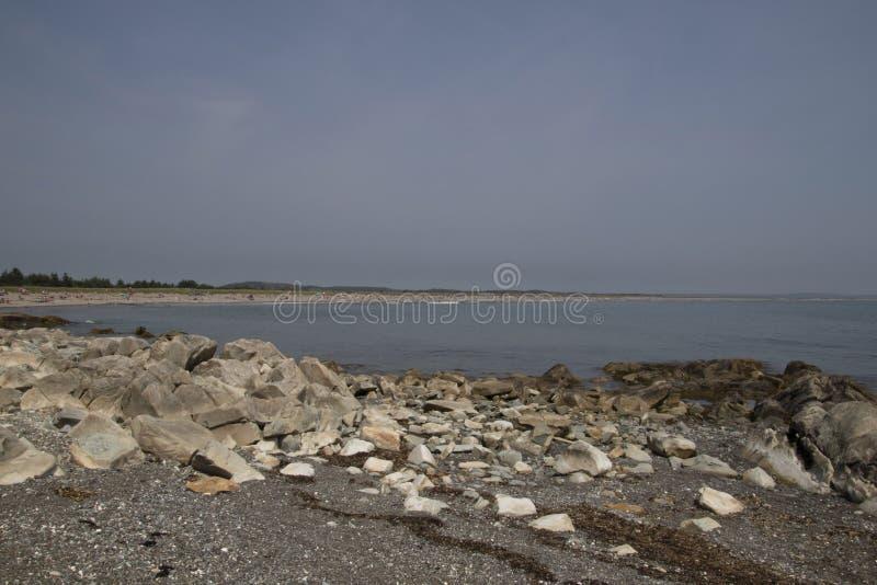 Μια άποψη του ωκεανού που βλέπει πέρα από ένα πρώτο πλάνο των βράχων και του αμμοχάλικου στοκ φωτογραφία με δικαίωμα ελεύθερης χρήσης