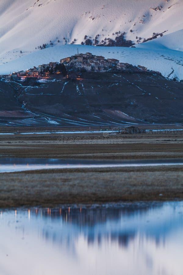 Μια άποψη Castelluccio Di Norcia μπροστά από έναν μεγάλο εχιόνισε mountaind και απεικόνισε σε μια λίμνη στην κοιλάδα στοκ εικόνες