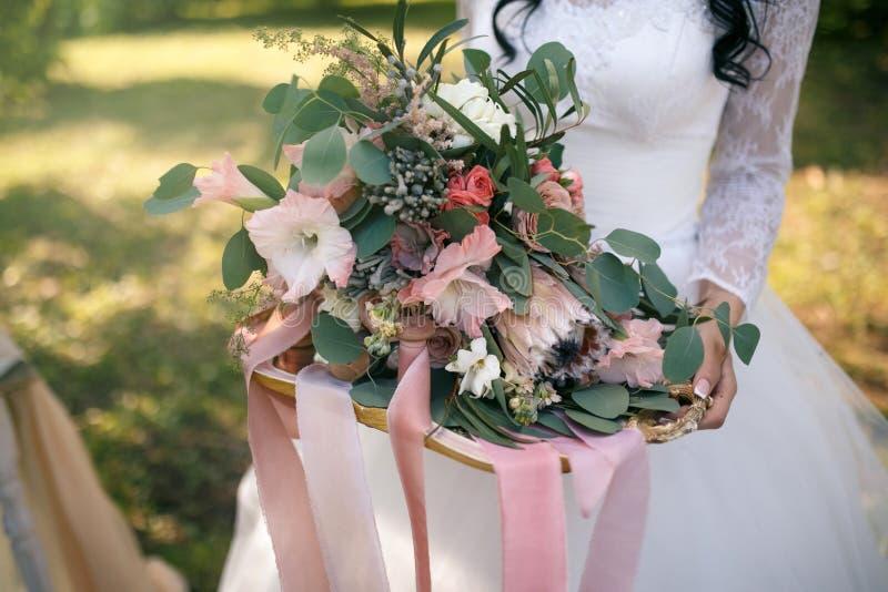 Μια άφθονη γαμήλια ανθοδέσμη των εξωτικών λουλουδιών σε έναν χρυσό δίσκο που διακοσμείται με τις ρόδινες κορδέλλες στα χέρια της  στοκ φωτογραφία με δικαίωμα ελεύθερης χρήσης