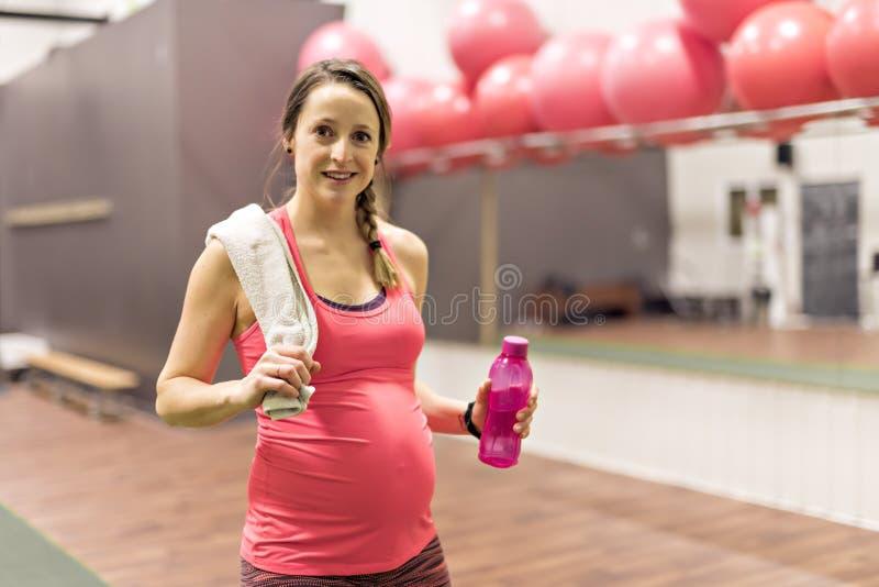 Μια έγκυος γυναίκα κάνει τις ασκήσεις στη γυμναστική στοκ εικόνες