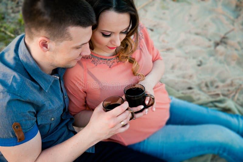 Μια έγκυος όμορφη γυναίκα που στηρίζεται υπαίθρια στοκ φωτογραφία