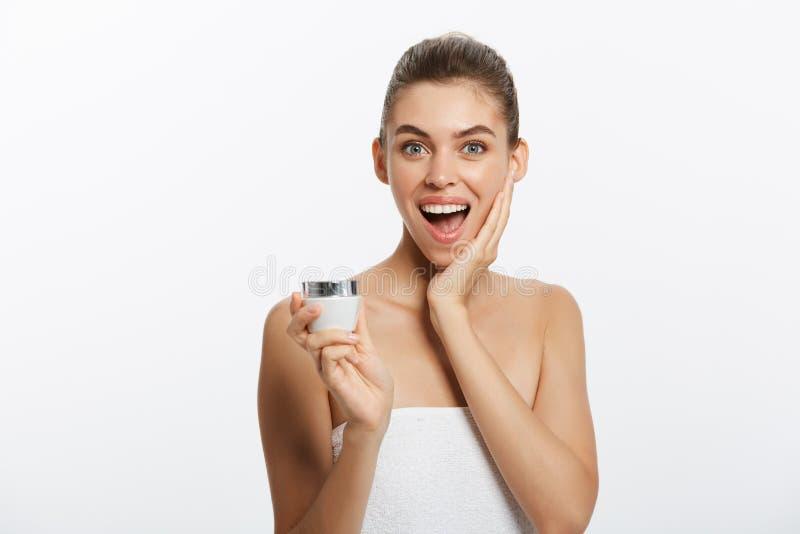 Μια έκπληκτη γυναίκα με μια πετσέτα στο σώμα της εφαρμόζει μια κρέμα στο δέρμα προσώπου στοκ εικόνες