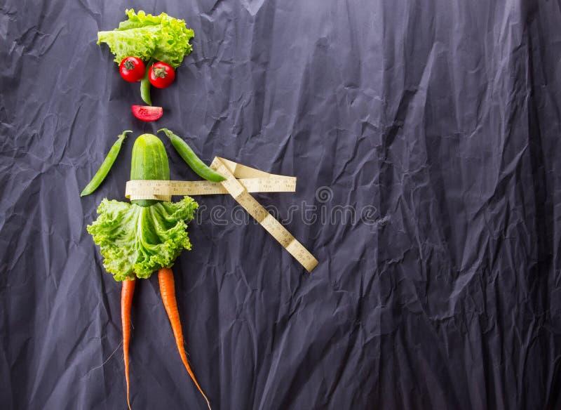 Μια έννοια τροφίμων του κοριτσιού με τα λαχανικά στο μαύρο υπόβαθρο εγγράφου Απώλεια βάρους και υγιής τρόπος ζωής Με το διάστημα  στοκ φωτογραφία