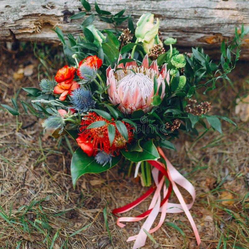 Μια αγροτική γαμήλια ανθοδέσμη με τις ρόδινες κορδέλλες κοντά στο κούτσουρο _ στοκ φωτογραφίες με δικαίωμα ελεύθερης χρήσης