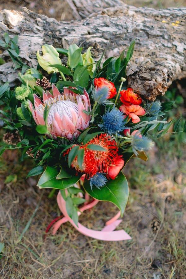 Μια αγροτική γαμήλια ανθοδέσμη με τις ρόδινες κορδέλλες κοντά στο κούτσουρο _ στοκ εικόνες με δικαίωμα ελεύθερης χρήσης