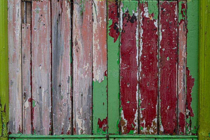 Μια αγροτική ξεπερασμένη ξύλινη πόρτα επιτροπής με την αποφλοίωση χρωμάτων από την αναχώρηση των στρωμάτων των διαφορετικών χρωμά στοκ φωτογραφίες με δικαίωμα ελεύθερης χρήσης