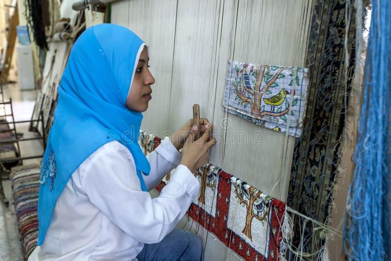 Μια αιγυπτιακή κυρία μελετά το σχέδιο του μάλλινου τάπητα που κάνει σε ένα εργοστάσιο στο Κάιρο, Αίγυπτος στοκ εικόνα