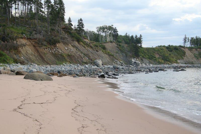 Μια αμμώδης παραλία που οδηγεί σε μια δύσκολη παραλία στοκ εικόνα