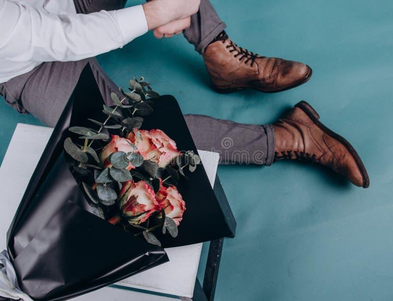 Μια ανθοδέσμη των τριαντάφυλλων βρίσκεται σε μια καρέκλα κοντά στα shos τύπων στοκ φωτογραφία με δικαίωμα ελεύθερης χρήσης