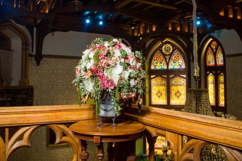 Μια ανθοδέσμη των τριαντάφυλλων λευκού, ροζ και τσαγιού με τους κλάδους σε ένα παλαιό βάζο στα πόδια στοκ φωτογραφία με δικαίωμα ελεύθερης χρήσης