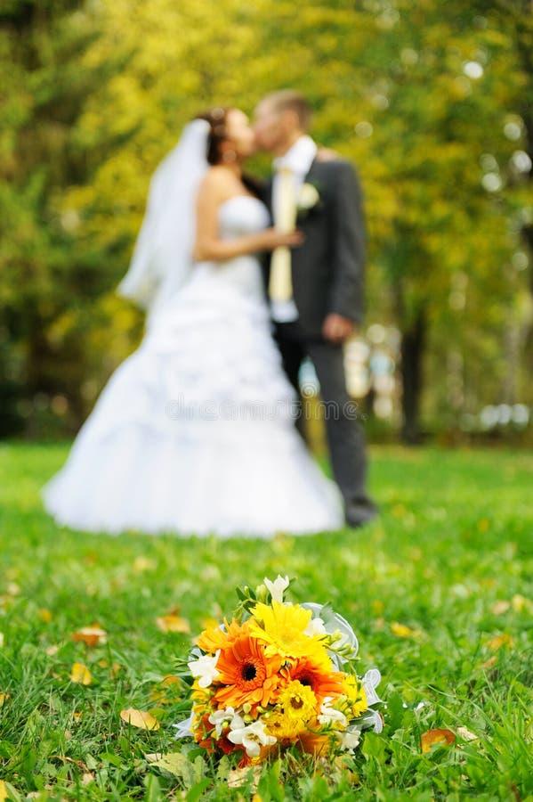 Μια ανθοδέσμη για τη νύφη στο υπόβαθρο του ζευγαριού φιλήματος στοκ φωτογραφίες