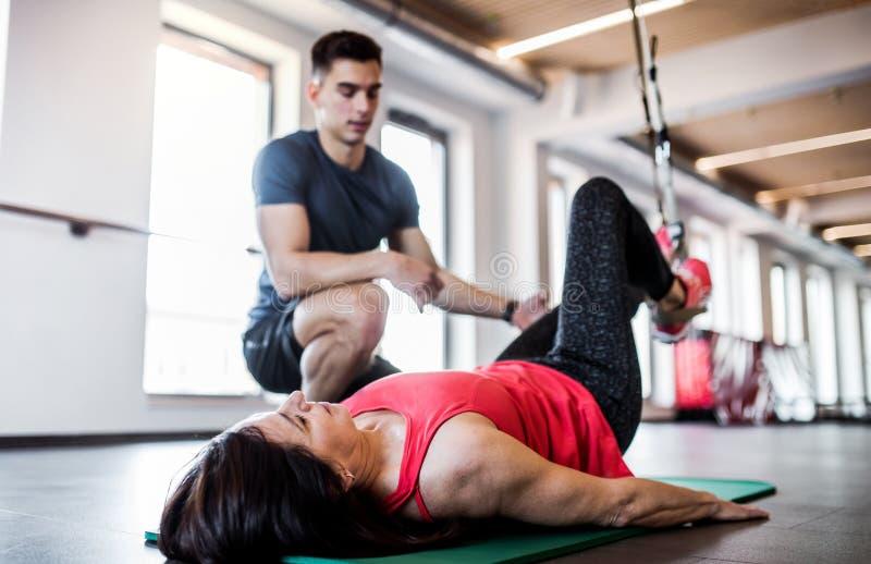 Μια ανώτερη γυναίκα στη γυμναστική και ένας προσωπικός εκπαιδευτής που κάνει την άσκηση με TRX στοκ εικόνα με δικαίωμα ελεύθερης χρήσης