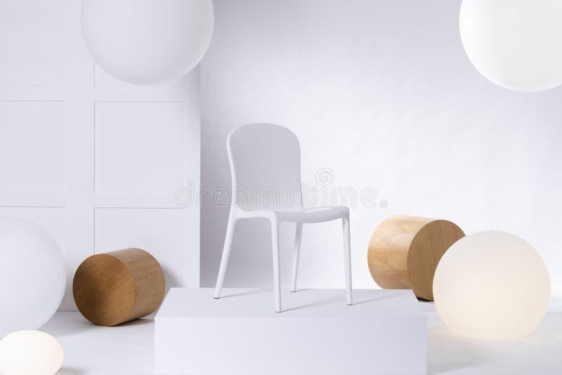 Μια απλή, πλαστική, άσπρη καρέκλα που στέκεται σε μια εξέδρα στο άσπρο κλίμα Πραγματική φωτογραφία της παρουσίασης επίπλων σε ένα στοκ φωτογραφία με δικαίωμα ελεύθερης χρήσης