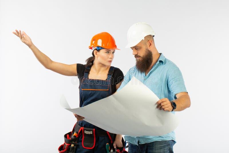 Μια αρσενική συνεδρίαση των αρχιτεκτόνων ή μηχανικών με έναν χτίζοντας ανάδοχο γυναικών στο άσπρο υπόβαθρο στοκ εικόνα με δικαίωμα ελεύθερης χρήσης