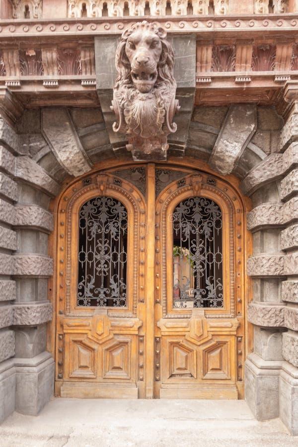 Μια αρχαία βαλανιδιά σχημάτισε αψίδα την διπλός-βγαλμένη φύλλα πόρτα στοκ εικόνες