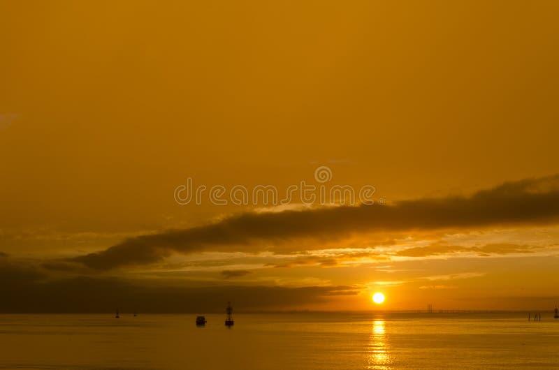 Μια βάρκα κάτω από τον ήλιο ρύθμισης στοκ εικόνες