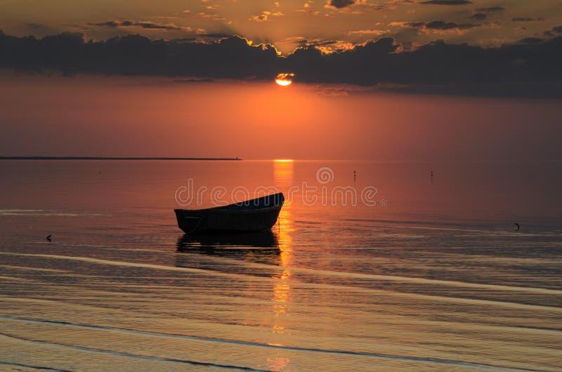 Μια βάρκα κοντά στην ακτή της θάλασσας της Βαλτικής στο ηλιοβασίλεμα, Λετονία, Jurmala στοκ εικόνα με δικαίωμα ελεύθερης χρήσης