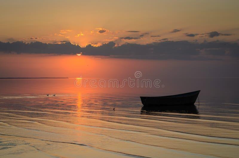 Μια βάρκα κοντά στην ακτή της θάλασσας της Βαλτικής στο ηλιοβασίλεμα, Λετονία, Jurmala στοκ φωτογραφίες
