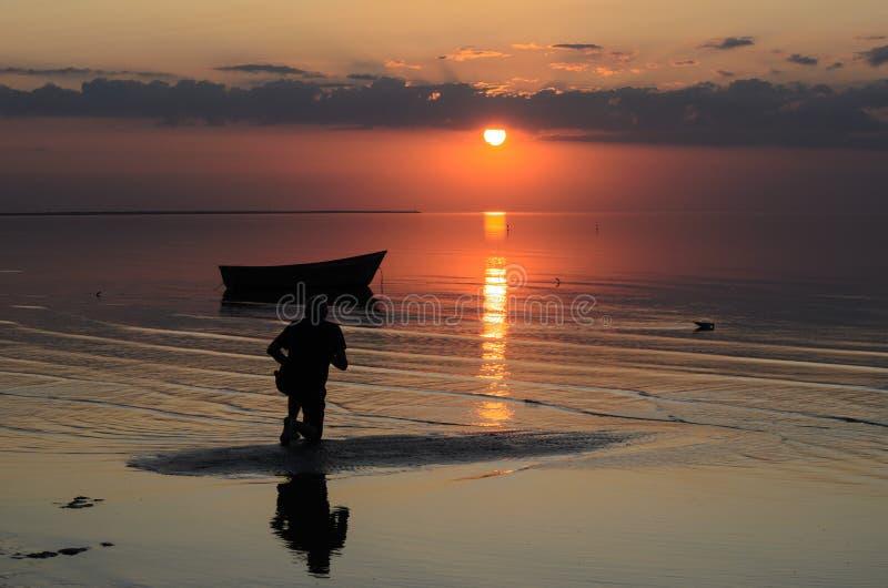 Μια βάρκα κοντά στην ακτή της θάλασσας της Βαλτικής στο ηλιοβασίλεμα, Λετονία, Jurmala στοκ εικόνα