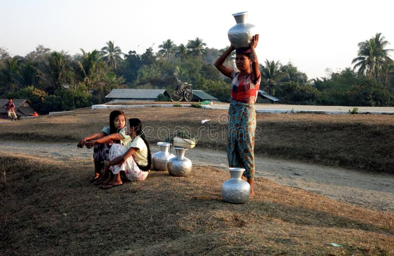 Μια βιρμανίδα γυναίκα που βάζει το σύνολο βάζων του νερού στο κεφάλι της στοκ εικόνα με δικαίωμα ελεύθερης χρήσης