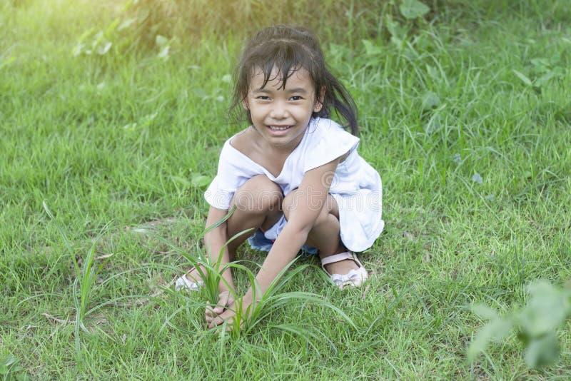 Μια βοήθεια κοριτσιών που καλλιεργεί με το κάθισμα βγάζει τα ζιζάνια στο χορτοτάπητα στοκ εικόνα