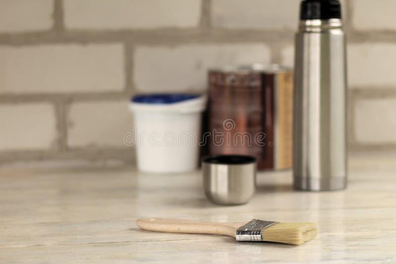 Μια βούρτσα βρίσκεται δίπλα σε έναν πλαστικό κάδο χρωμάτων με ένα μπλε καπάκι, ένα μέταλλο μπορεί, thermos με ένα φλυτζάνι παλαιό στοκ φωτογραφίες