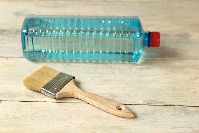 Μια βούρτσα βρίσκεται δίπλα σε ένα διαφανές πλαστικό μπουκάλι με έναν διαλύτη σε έναν παλαιό άσπρο εκλεκτής ποιότητας ξύλινο πίνα στοκ εικόνες